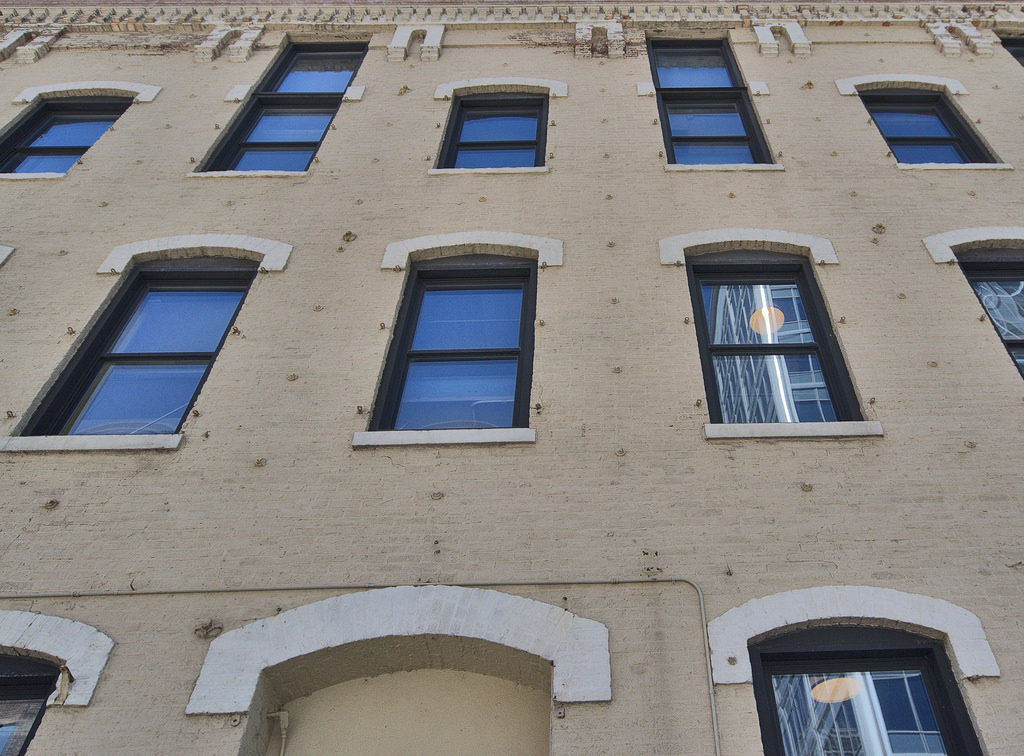 Facade detail of 154 - 166 North Jefferson Street. Note the anchor bolts spaced evenly across the wall and layered brick corbelling on the cornice.